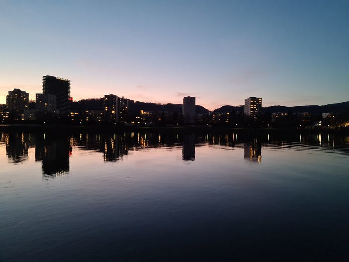 Reflection of illuminated buildings in river at sunset