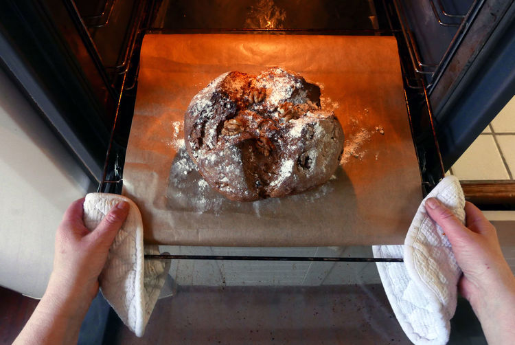 Cropped hands of woman baking bread in microwave at home