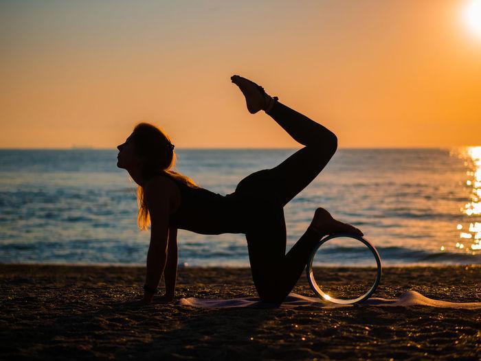 Silhouette woman doing yoga at beach against sky