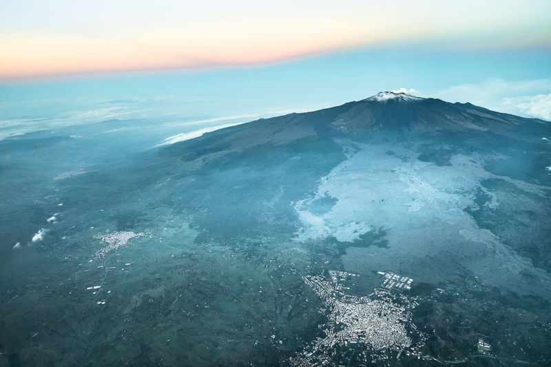 Aerial view of volcanic crater against sky during sunset