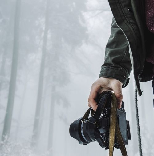 Cropped Image Of Man Holding Camera At Forest During Foggy Weather