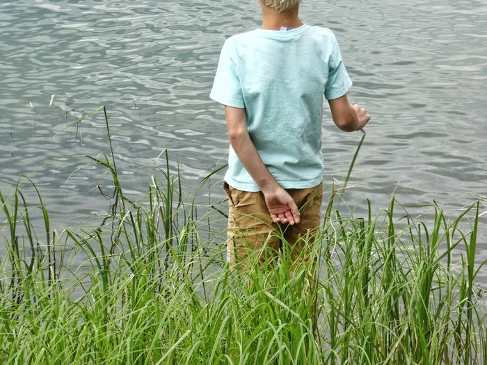 In touch with nature One Person Casual Clothing Water Nature Standing Lake Grass Rear View Boy Standing Still Looking At The Lake Silent Moment Grouth Midsection Part Of Body Shirt Outdoors Beauty In Nature EyeEm Gallery Just Life  The Portraitist - 2017 EyeEm Awards Childhood Sommergefühle