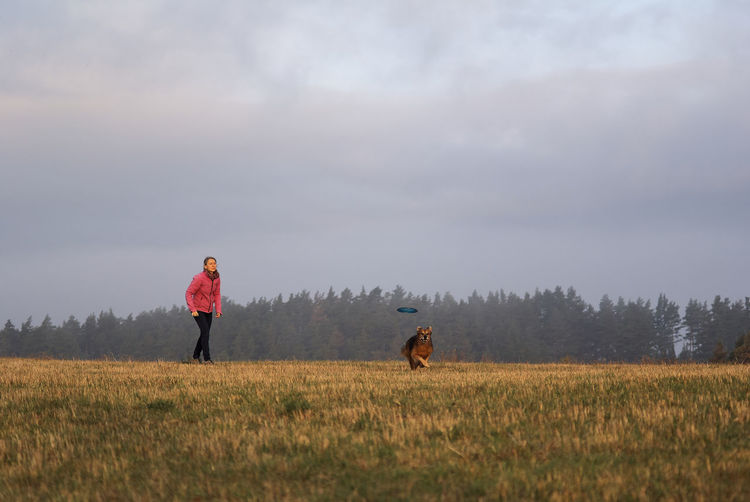 Woman with dog playing on agricultural field