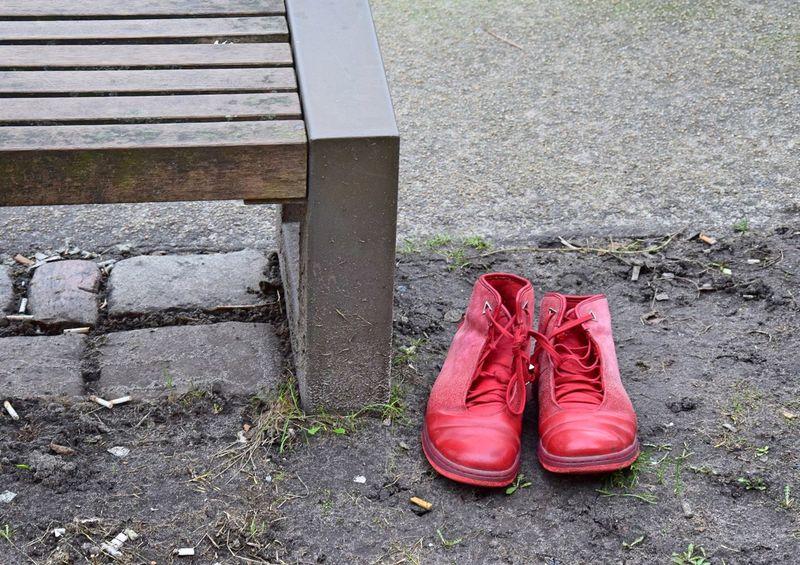 Die Schuhe waren ordentlich neben einer Bank in einem Park abgestellt. Welche Geschichte mag sich dahinter verbergen? Bench City Life Lost Red Shoes Beside Contrast Contrast Colors Park Seat