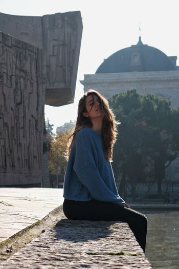 Portrait of young woman sitting against built structure
