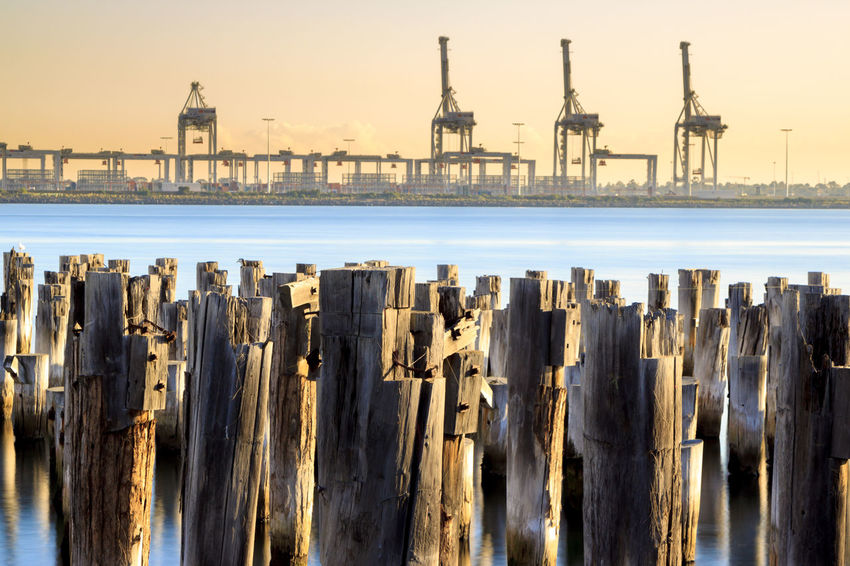 Princes Pier with cranes in the background Architecture Beach Building Exterior Built Structure Fuel And Power Generation Industry Land Nature No People Outdoors Pier Post Sea Sky Sunset Water Waterfront Wooden Post