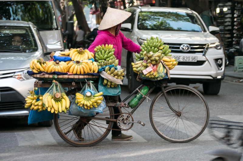 Banana Bananenstaude Banane Bicycle Working Woman Woman Vietnamese Streetphotography Street Photography Transportation Retail  City Mode Of Transportation Food And Drink One Person Street Day Road Hat Outdoors Adult Vietnam Hanoi On The Streets On The Street International Women's Day 2019