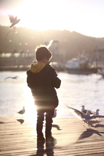 Boy standing on pier over lake against sky during sunset