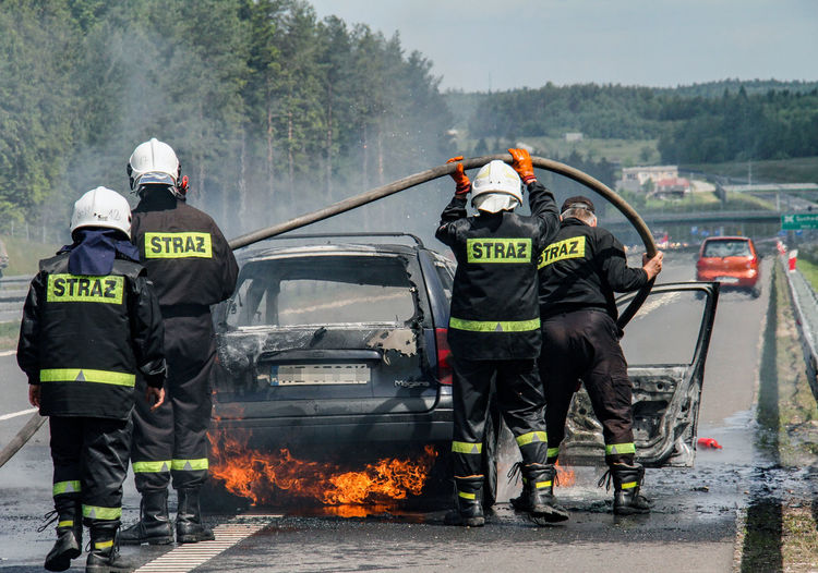 Firefighters standing at burning car on road