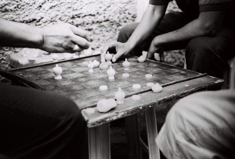 Midsection of friends playing board game while sitting outdoors