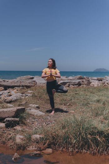 Women on beach against clear sky doing yogq