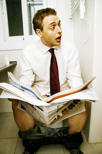 Shocked Young Man Reading Newspaper On Toilet Seat
