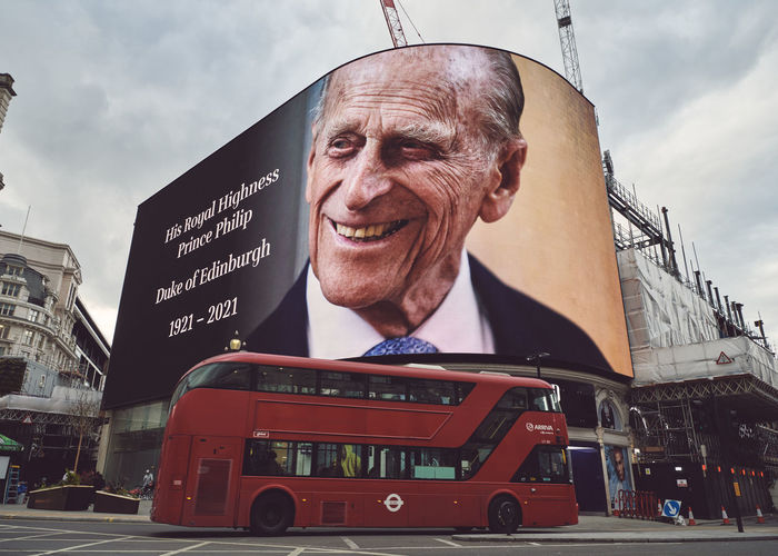 Low angle portrait of smiling man in city against sky