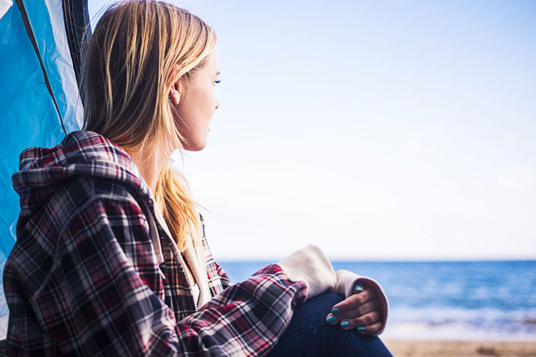 Young woman sitting at beach against clear sky