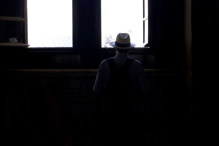 Rear view of man whit hat standing against window in istanbul