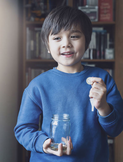 Smiling boy holding coin while standing at home