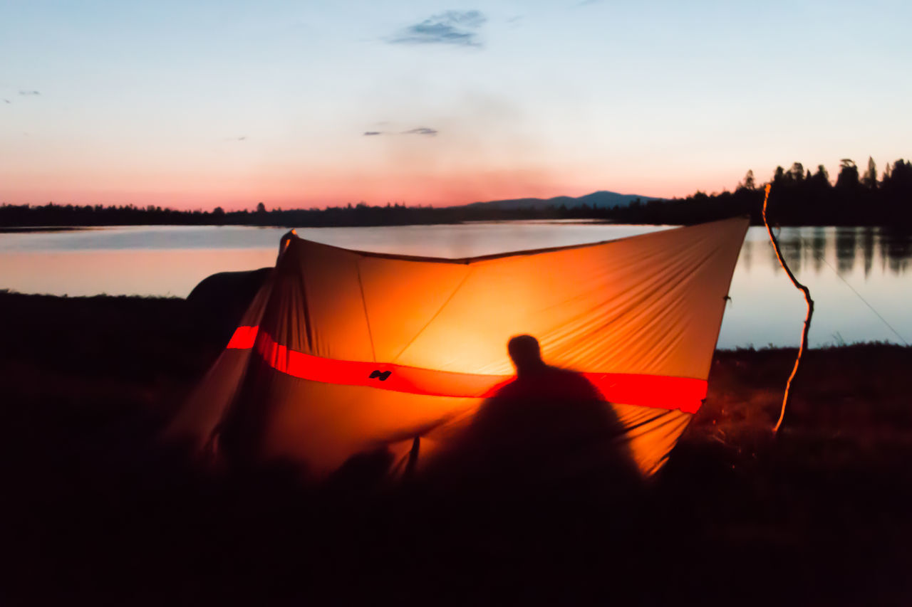 Shadow of person in illuminated tent at lakeshore during sunset