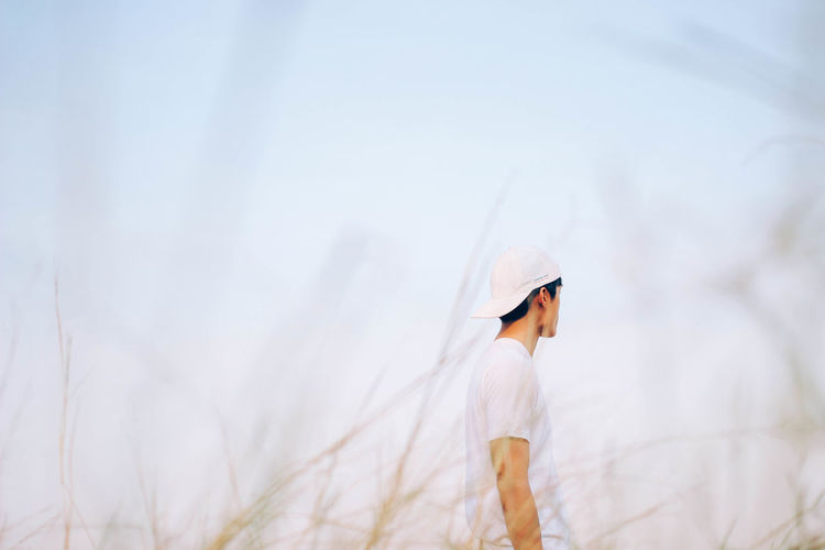 man wearing white t-shirt, cap standing on the field, copy space Copy Space EyeEm Best Shots EyeEm Nature Lover Man Adult Beauty In Nature Cap Casual Clothing Day Focus On Foreground Leisure Activity Lifestyles Nature One Person Outdoors People Real People Side View Sky Standing Young Adult Young Women