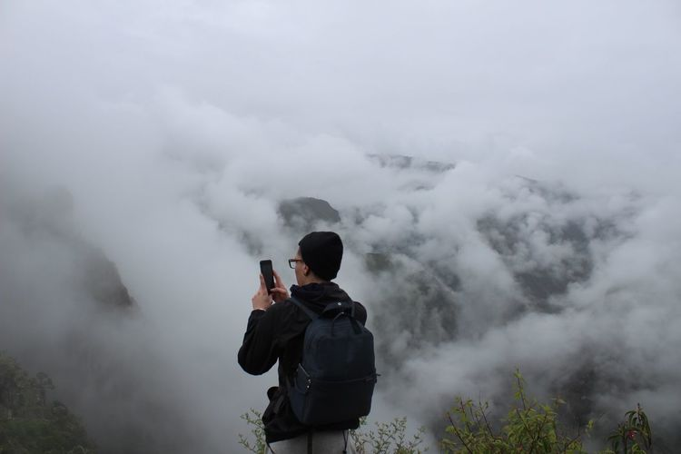 Rear view of man photographing in foggy weather