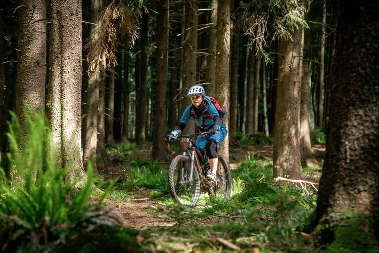 Young woman riding a mountain bike on footpath in the forest. salzburg, austria.