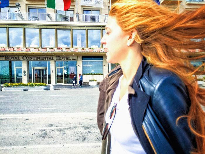 Side view of young woman in city against sky
