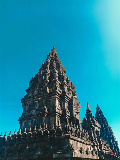 Low angle view of historical building against blue sky candi prambanan indonesia