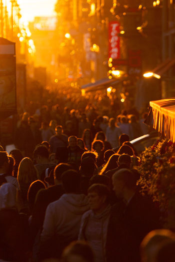Crowd on street in city at sunset