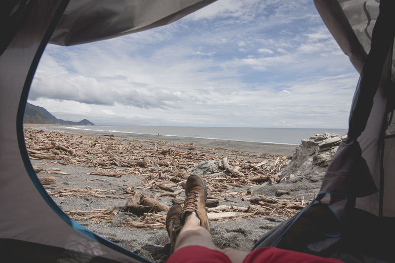 Low section of man lying in tent at beach against sky