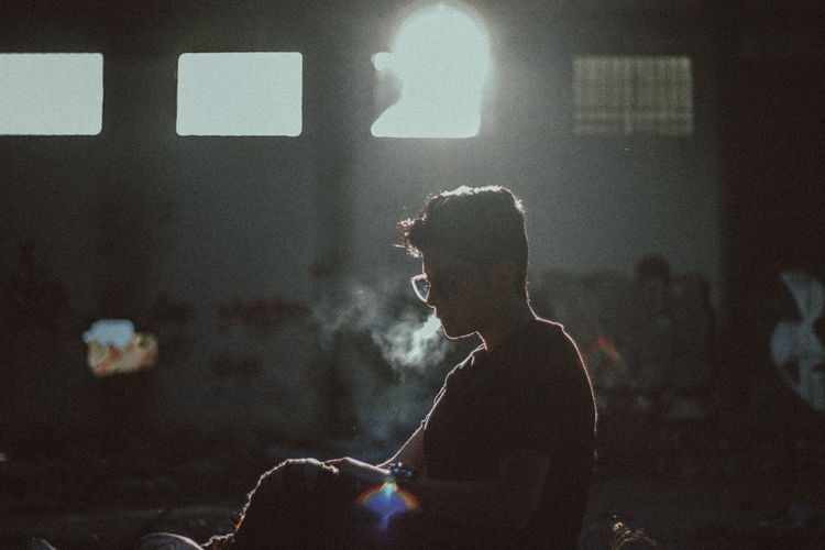 Side View Of Man Smoking In Room