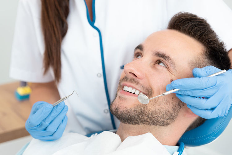 Dentist examining smiling patient at clinic