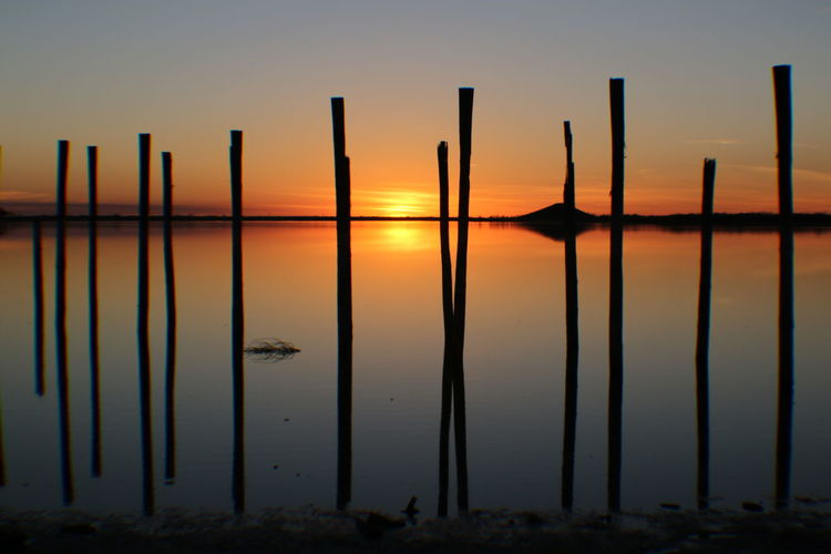 Silhouette wooden posts in sea against sky a sunset