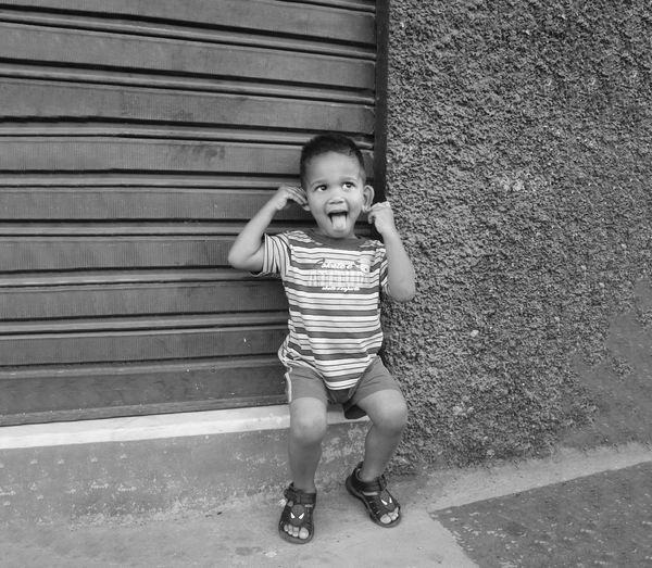 Boy Sticking Out Tongue While Sitting By Closed Shutter