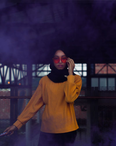 Portrait of young woman wearing sunglasses while standing amidst smoke