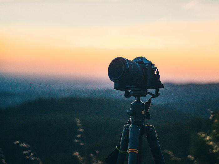 Close-up of camera on tripod against sky during sunset