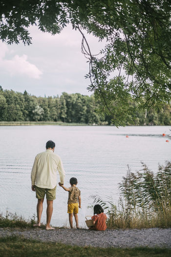 Rear view of father and daughter in lake
