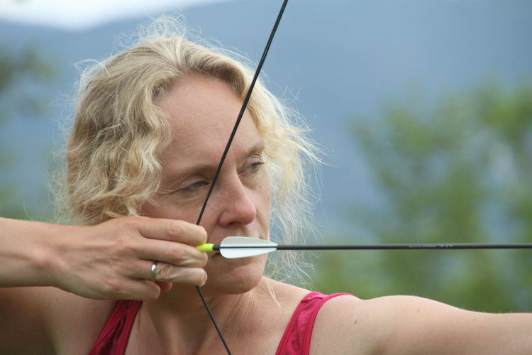 Self Portrait Woman Portrait Archery Bow Arrow Focused Concentration Contemplative Leisure Activity Headshot One Person Holding Blond Hair Young Adult Front View Adult Focus On Foreground Lifestyles Real People Close-up Activity Outdoors Human Connection The Portraitist - 2019 EyeEm Awards