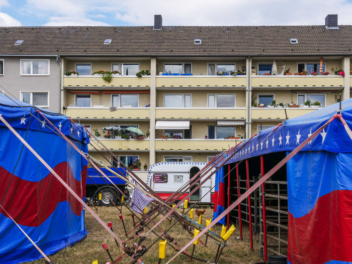 URBANANA #urbanana: The Urban Playground Circus Apartment Architecture Available Light Blue Building Building Exterior Built Structure City Clothesline Clothing Day Flag Hanging Mode Of Transportation Nature No People Outdoors Railing Residential District Sky Streetphotography Transportation Window
