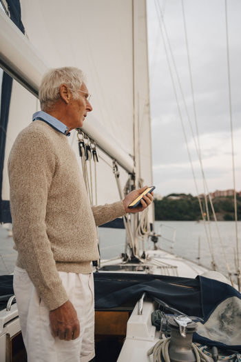 Side view of man looking at sailboat