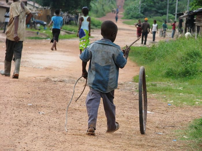 Rear view of boy playing with tire while walking on field