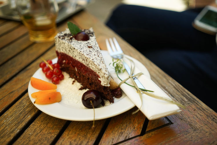 High Angle View Of Cake With Fruits Served In Plate On Table