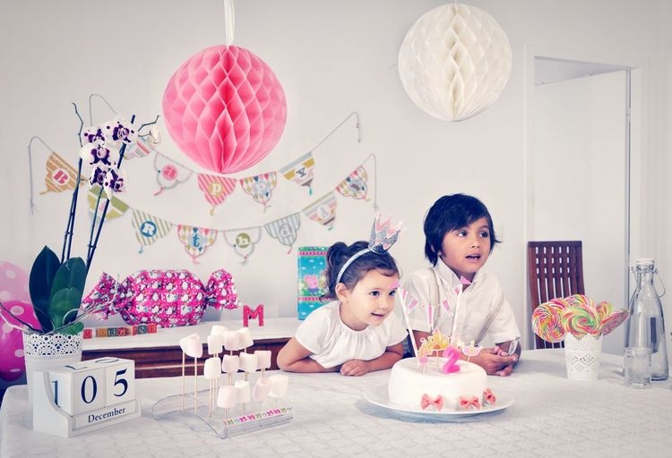 Siblings with cake sitting at table during birthday celebration