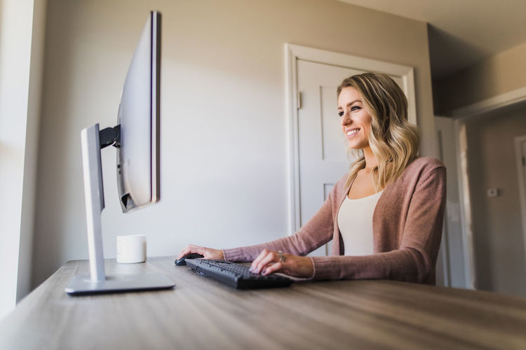 Woman using phone while sitting on table at home