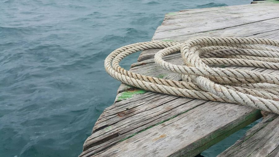 Close-up of rope on pier over sea