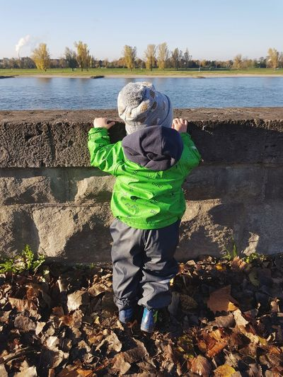 Curiosity Child Boys Water Childhood Outdoors Warm Clothing Nature Sky Hat Headgehog River Shore Boats The Week On EyeEm Winter EyeEm Best Shots Happiness Curiosity Mommylife Nautical Vessel Rear View Silhouette From My Point Of View Toddler  Growing Up