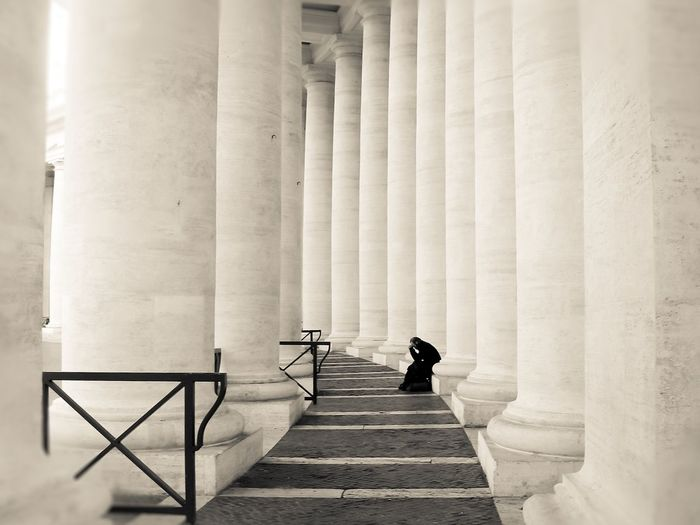 Mid distance view of man sitting by columns at colonnade