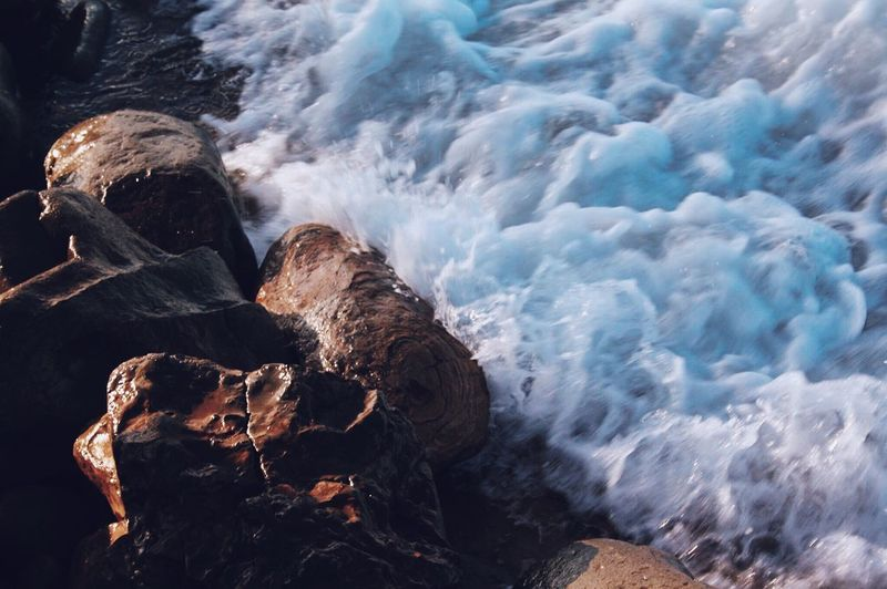 High angle view of surf on rocky shore