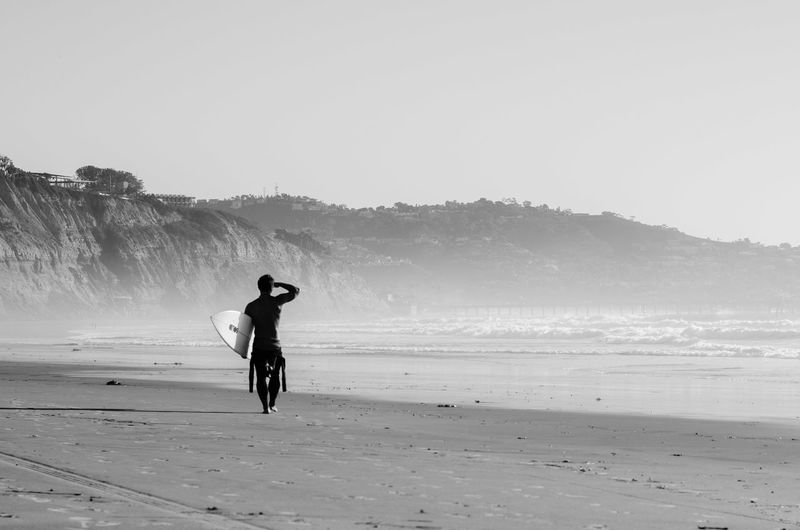 Rear view of man walking with surfboard at beach