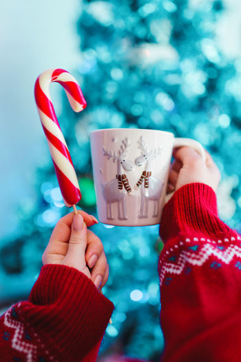 Girl holding cup with deers of tea or cocoa and lollipop on Christmas tree background Holding Human Hand One Person Hand Red Human Body Part Real People Personal Perspective Celebration Candy Cane Focus On Foreground Food And Drink Christmas Unrecognizable Person Close-up Sweet Food Lifestyles Human Finger Sweet Finger Temptation Nail
