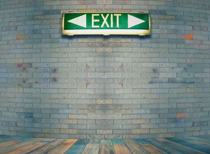 Exit sign against brick wall