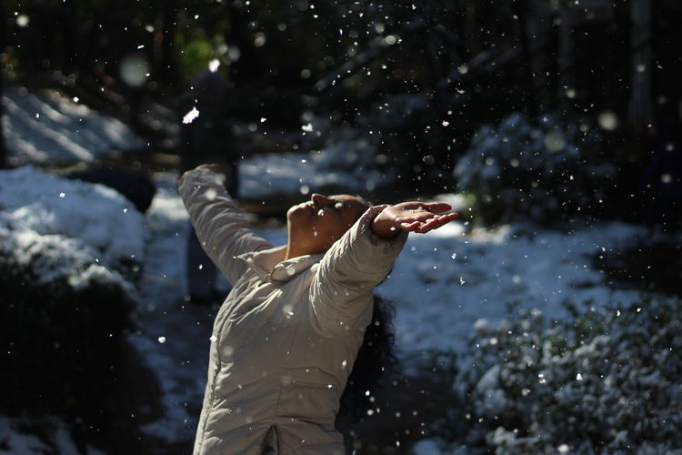 Woman with arms outstretched wearing warm clothing during winter